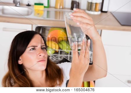 High Angle View Of Young Woman Looking At Clean Glass In Kitchen