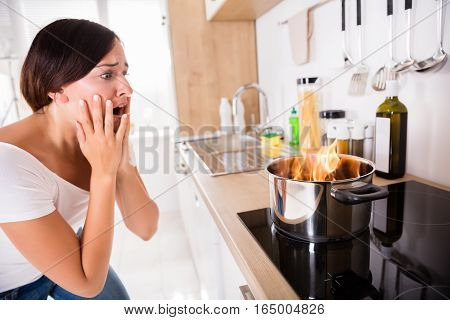 Shocked Young Woman Looking At Burnt Food In Cooking Pot