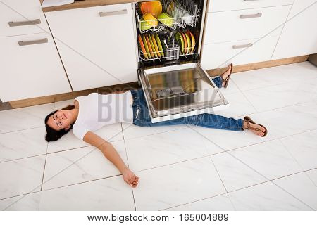 High Angle View Of Young Woman Lying On Floor Under A Dishwasher