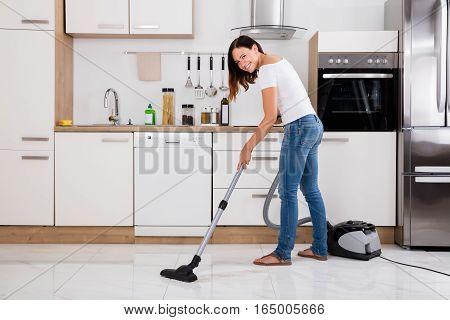 Young Happy Woman Using Vacuum Cleaner To Clean The Floor In The Kitchen