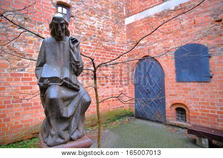 VILNIUS, LITHUANIA - JANUARY 2, 2017: A courtyard in the former small Jewish Ghetto with a statue of Metrastininkas (sculptor Vaclovas Krutinis)