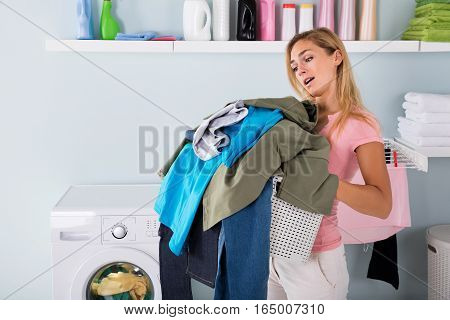 Young Tired Unhappy Woman Holding A Bucket Of Dirty Clothes In Laundry Room