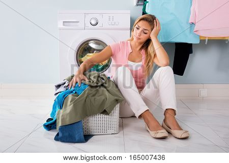 Young Unhappy Woman Looking At Pile Of Clothes Near Washing Machine At Utility Room