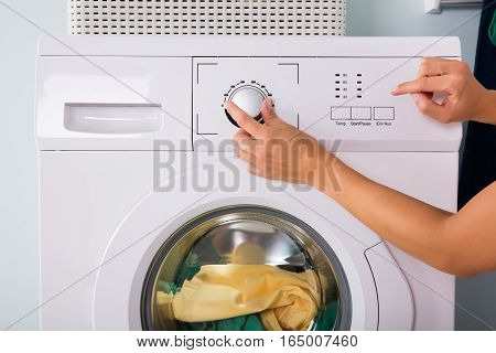 Close-up Of Person Hand Pressing Button Of Washing Machine For Laundry