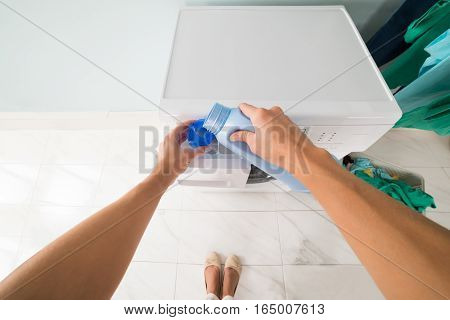 POV Perspective Of Woman Pouring Detergent In A Lid Near Washing Machine In Laundry Room
