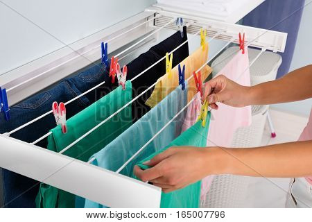 Close-up Of Woman Hanging Wet Clean Cloth On Clothes Line In laundry Room