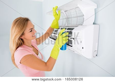 Young Happy Woman Cleaning The Air Conditioner With Spray Bottle At Home