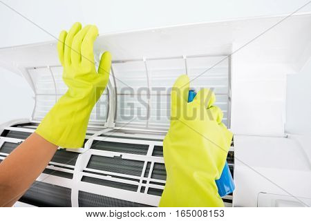 Close-up Of Person Hand Cleaning The Air Conditioner With Spray Bottle At Home