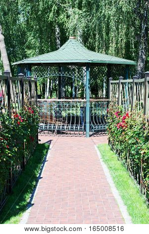 paving path with rose bushes to the gazebo in the park