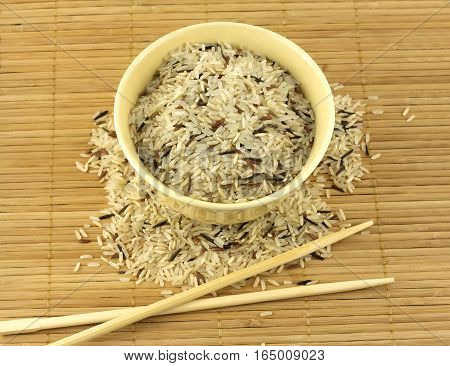 China color rice and beige bowl with chopsticks on brown straw mat top view closeup