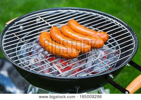 View from above on a green grass background of a row of pork and beef bratwurst grilling over a barbecue fire on a hot day during the summer vacation