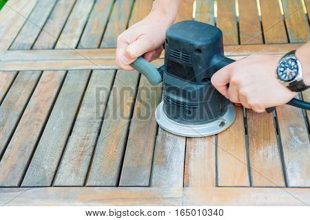 Close-up of carpenter's hands working with electric sander - polishing old color from wooden table