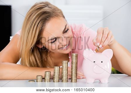 Young Happy Woman Inserting Coin In The Piggybank Near Stack Of Coins On Desk
