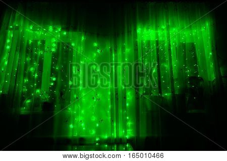 Led luminous garland with green lights on a dark room wooden background.
