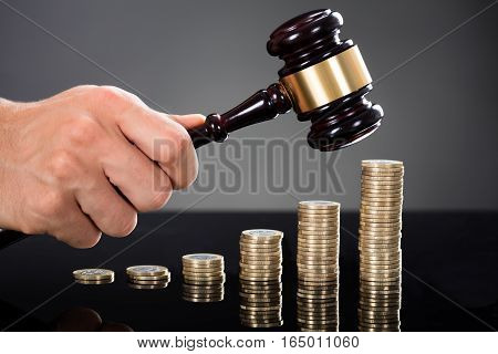 Close-up Of A Judge Hands Hitting Gavel In Front Of Stacked Coins At Desk