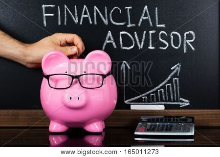 A Person Inserting Coin In Piggybank Showing Financial Advisor Concept On Blackboard