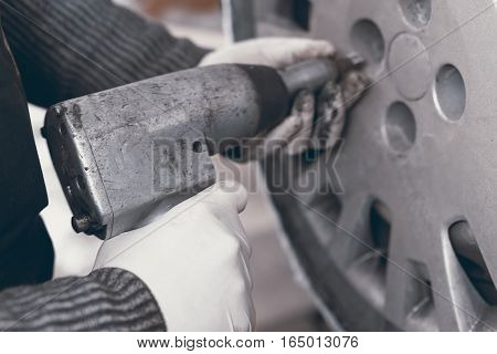 Professional car mechanic changing car wheel. changing car wheel