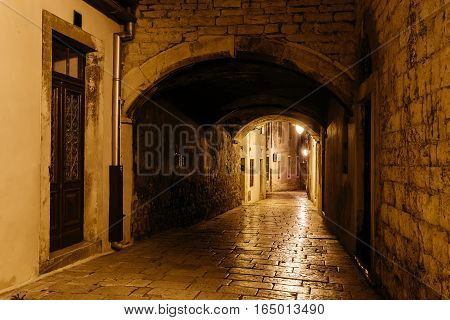 empty night narrow European street with archway in the center of Sibenik, Croatia.