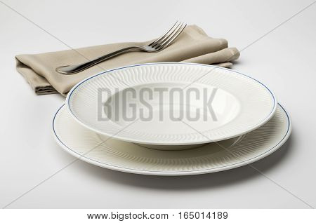 Empty round white plate and bowl with napkin and fork on white table