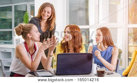 Group of four pretty businesswomen working togeather with new startup project using laptop computer in modern loft. People and teamwork concept - happy creative team in office. Casually dressed female colleagues talking in a meeting room.