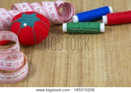 One red pincushion, tape and several threads with needle are on the light wooden background