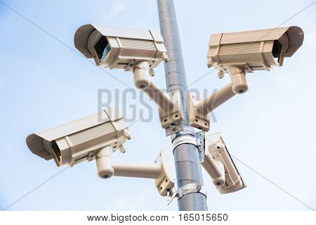 Low Angle View Of Four Security Camera Installed On Pole
