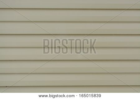 In the corrugated sheet fence made of beige metal sheets without screws. The texture of the metal profile. Profiled metal.