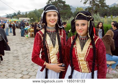 MTSKHETA, GEORGIA - OCT 14, 2016: Two happy girls in traditional Georgian costumes ready for performance during party on the City Day on October 14, 2016. Mtskheta has a population 20.000