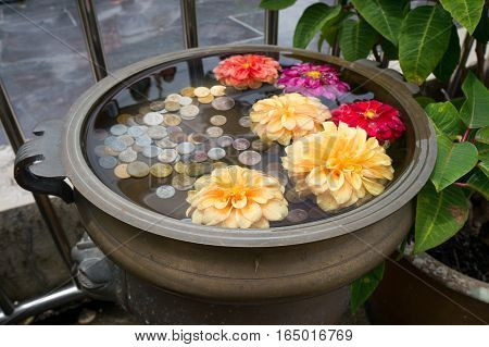 A small floral wishing well with coins on Penang Hill Malaysia