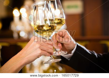 happy couple have a romantic date in a fine dining restaurant they drink wine and clinking glasses, cheers - closeup