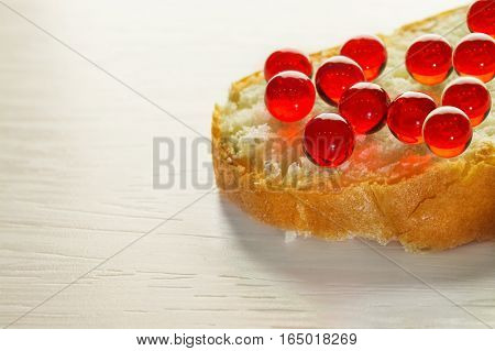 Sandwich with red caviar on white bread on a white tree, selective focus