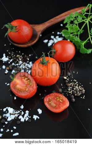 Cherry tomato with salt and black pepper on black background