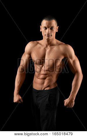Gym king. Vertical portrait of a young attractive bodybuilder posing shirtless smiling to the camera