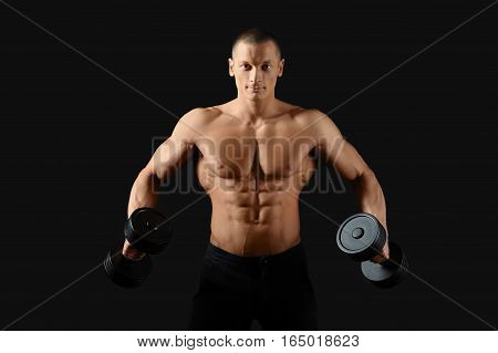 Broadening his back. Studio shot of an attractive young shirtless man pumping iron showing off his ripped abs