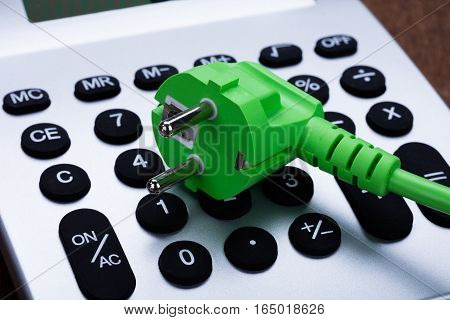 Close-up Of Green Eco Electric Cable On Calculator Button