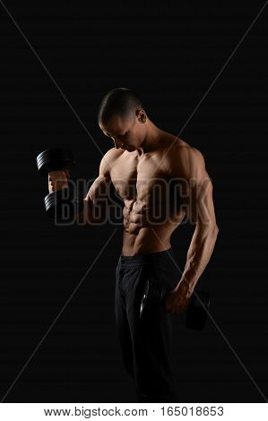 Devoted sportsman. Vertical shot of a hot and sexy shirtless muscular man posing on black background with dumbbells in his hands