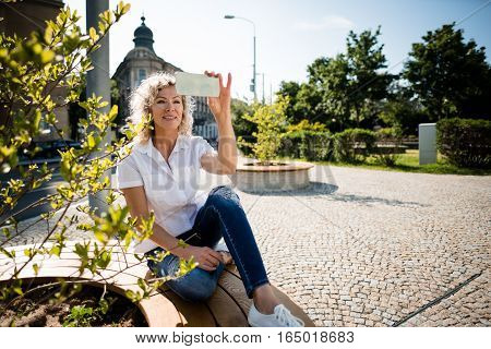 Smiling trendy mature woman posing for a selfie in park