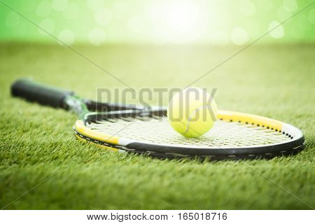 Close-up Of Tennis Racket With Green Ball On Grass