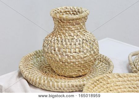 Crockery braiding of straw - a pitcher and a plate. Homemade ecological shatterproof tableware. poster