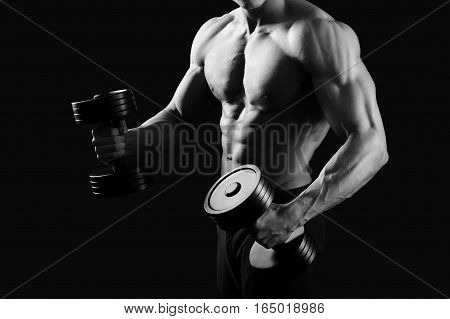 Willpower ON. Cropped black and white shot of a muscular male bodybuilder with perfect abs exercising with weights