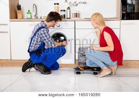 Woman Looking At Male Worker Checking The Defects In Washing Machine
