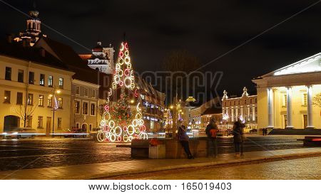 VILNIUS, LITHUANIA - JANUARY 2, 2017: A square in the Old town by night with the Town Hall on the right hand side and St Casimir's Church in the background