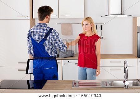 Smiling Customer Woman Shaking Hands With Male Plumber After Repair In The Kitchen