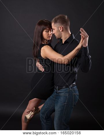 Young Couple Dancing On A Dark Background