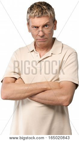 Casually dressed man with his arms folded in front of him scowling