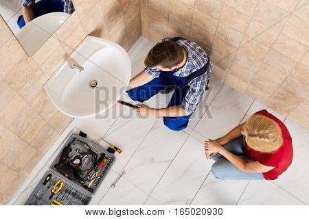 Woman Looking At Young Male Plumber Lying On Floor Fixing Sink In Bathroom