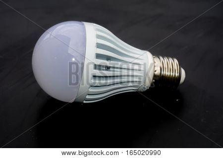 New energy saving light bulb on dark background.
