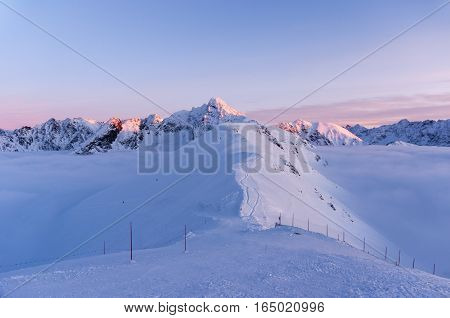 Big mountain peaks at sunset and inversion.