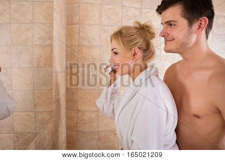 Young Smiling Couple Looking At Mirror Brushing Teeth Together In Bathroom At Home