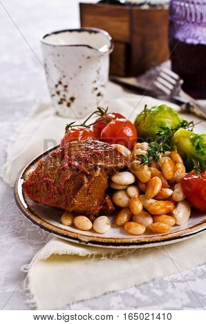 Meat stew with beans and vegetables in sauce. Selective focus.